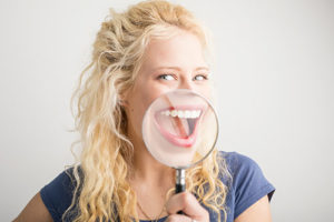 a woman smiling through a magnifying glass after getting dental bonding in missouri city tx